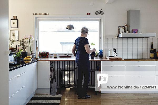 Durchgehende Rückansicht der älteren Frau  die in der Küche zu Hause steht.