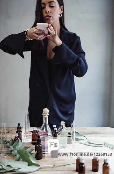 Mittlere erwachsene Unternehmerin beim Fotografieren von Parfümflaschen mit Smartphone auf dem Tisch gegen die Wand in der Werkstatt.