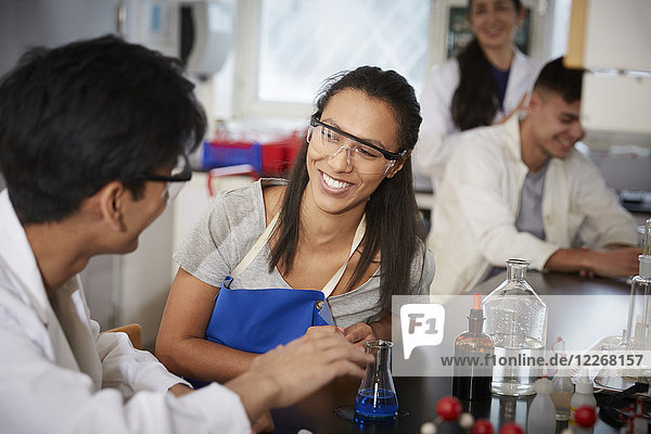 Lächelnde junge multiethnische Chemie-Studenten mit Lösungen im Labor der Universität