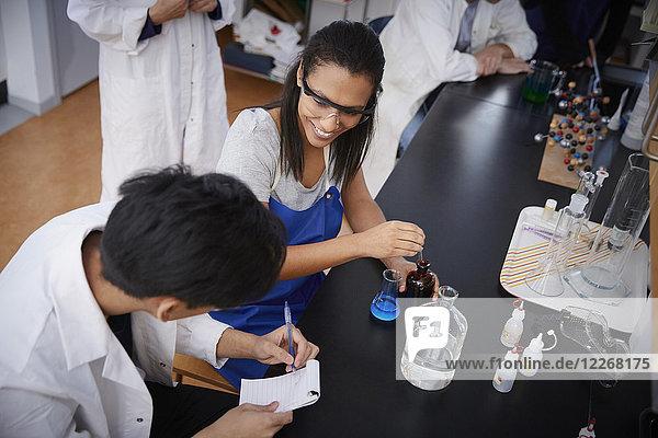 Hochwinkelansicht von lächelnden multiethnischen Studenten  die Lösungen mischen und in einem Spiralblock im Chemielabor schreiben.