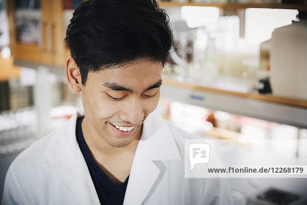 Lächelnder junger männlicher Student schaut auf das Chemielabor herab