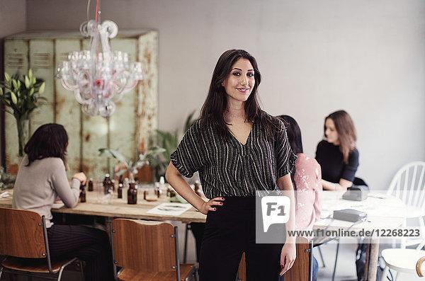 Porträt einer lächelnden jungen Frau  die in der Werkstatt mit der Hand auf der Hüfte steht.