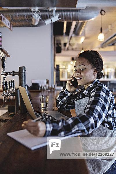 Lächelnde Managerin beim Telefonieren mit dem Laptop an der Theke