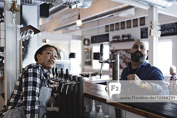 Barkeeperin mit männlichem Kunden im Stehen an der Theke