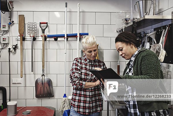 Female workers discussing over digital tablet while working in brewery
