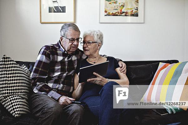 Seniorenpaar sitzt auf dem Sofa und teilt sich zu Hause ein digitales Tablett gegen die Wand.