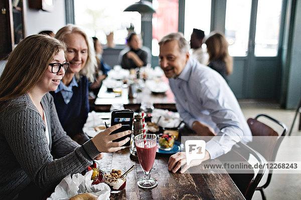 Lächelnde Tochter nimmt Selfie mit den Eltern mit  während sie am Tisch im Restaurant sitzt.