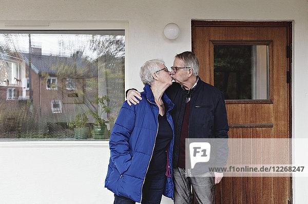 Seniorenpaar im Ruhestand küssend  während es sich gegen das Haus stellt.