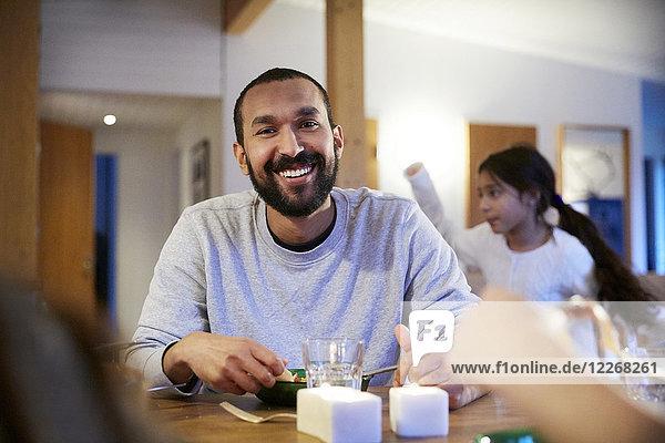 Lächelnder Mann beim Essen mit der Familie zu Hause