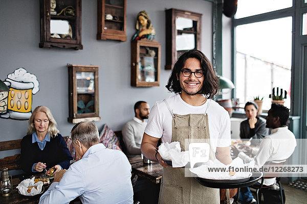 Porträt eines lächelnden jungen Kellners  der Essen serviert  während er gegen Kunden im Restaurant steht.