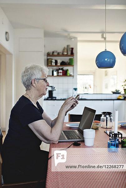 Seitenansicht der pensionierten Seniorin mit Smartphone im Sitzen mit Laptop am Esstisch
