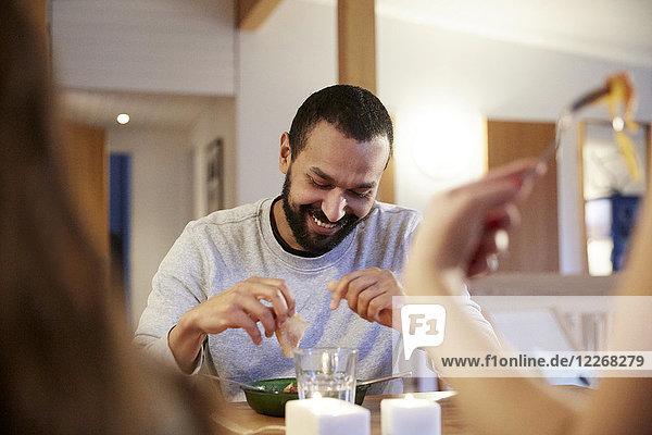 Lächelnder Mann beim Essen mit der Familie am Tisch