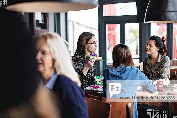 Junge multiethnische Freundinnen sitzend mit Geburtstagsgeschenken am Esstisch im Restaurant