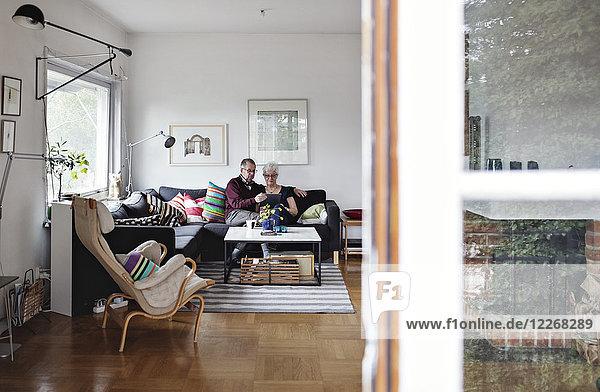 Seniorenpaar sitzt auf Sofa im Wohnzimmer zu Hause