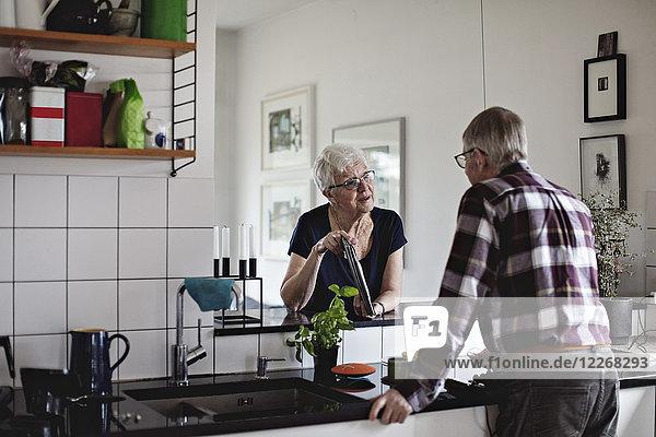 Senioren-Paar im Ruhestand am Küchentisch bei der Diskussion über digitale Tabletten