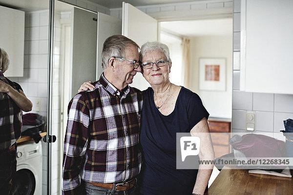 Porträt einer lächelnden älteren Frau  die mit einem Mann im Badezimmer steht.