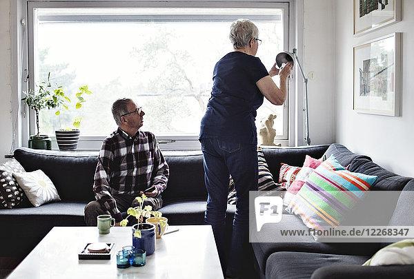 Senior Mann schaut auf die Frau  die die Stehleuchte am Sofa im Wohnzimmer verstellt.