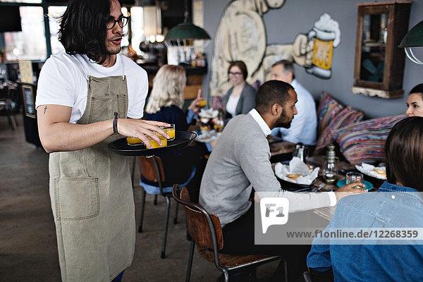 Junger Kellner  der Getränke serviert  während er im Restaurant gegen die Kunden steht.