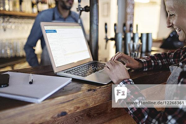 Lächelnder Manager mit Laptop an der Theke