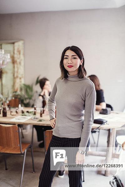 Porträt einer lächelnden jungen Frau  die mit der Hand auf der Hüfte gegen Kollegen in der Werkstatt steht.