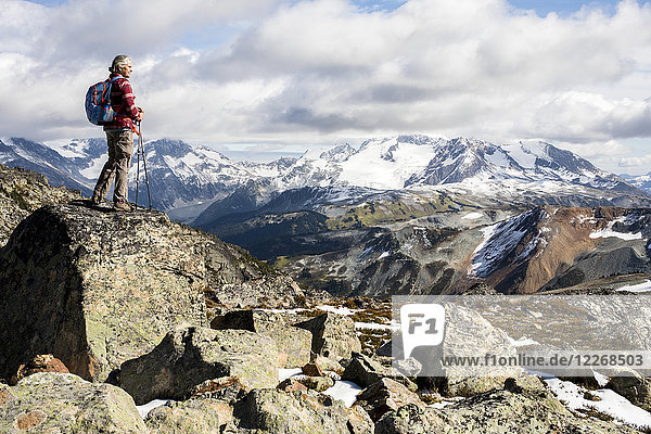 Female hiker looking at view of Garibaldi Provincial Park from top of Whistler Mountain  Whistler  British Columbia  Canada