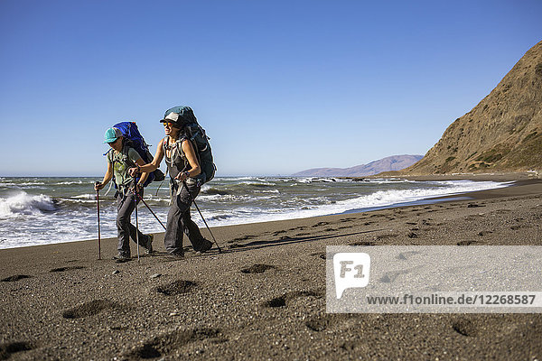 Two female hikers trekking side by side along Lost Coast beach  California  USA
