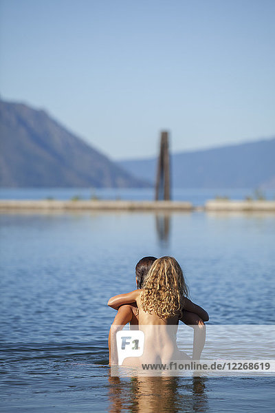 Mother giving naked daughter piggyback ride into lake  Sandpoint  Idaho  USA