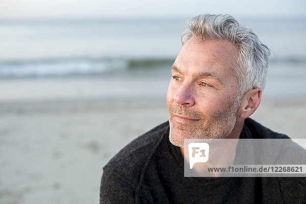 Portrait of gray-haired man sitting alone on coastal beach and looking away  Dennis  Massachusetts  USA