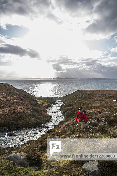 Backpacker hiking along creek on coastline  Torridon  Scotland  UK