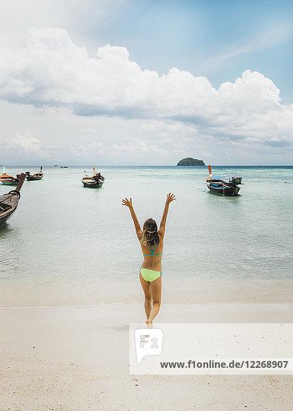 Young woman in bikini walking on beach towards sea with raised arms  Tambon Ko Tarutao  Chang Wat Satun  Thailand