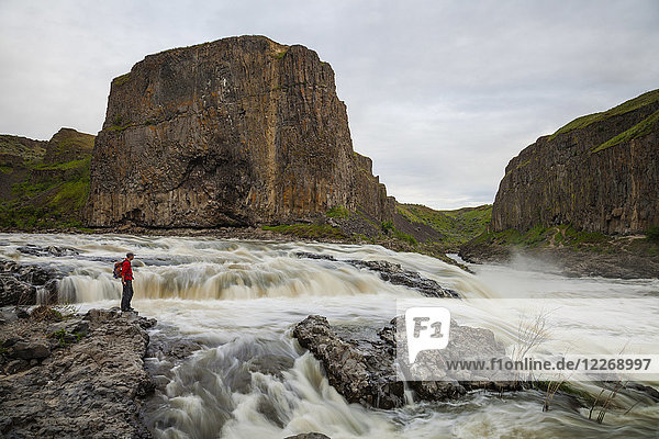 Hiker near river and rock formation in Palouse Falls State Park  Washington State  USA
