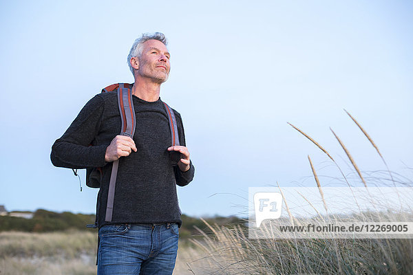 Mature man with gray hair and backpack at beach
