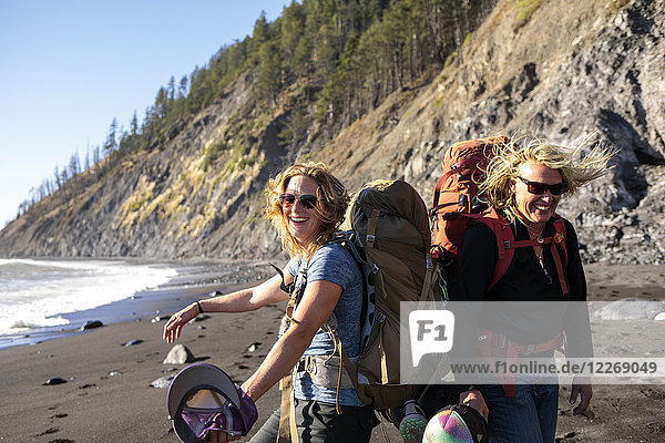 Female backpackers smiling while hiking along beach  Lost Coast Trail  Kings Range National Conservation Area  California  USA