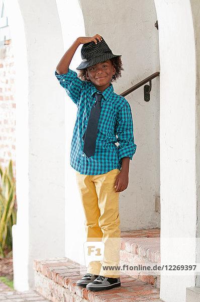Porträt eines Jungen,  der im Freien steht und einen Filzhut trägt