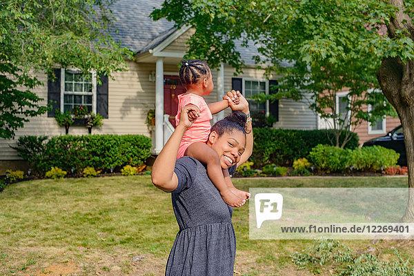 Mid adult woman in garden carrying baby daughter on shoulders  portrait