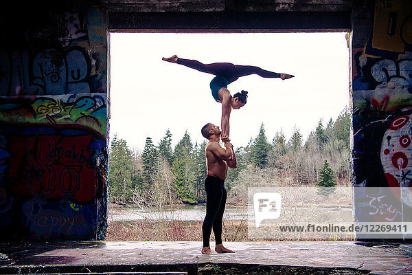 Couple practising acroyoga on outdoor stage