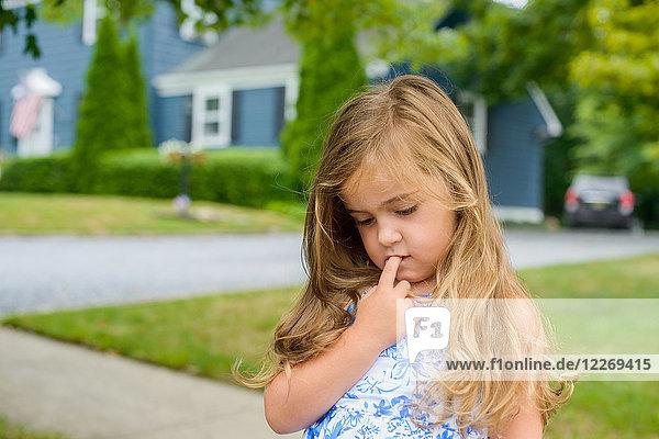 Mädchen mit Finger im Mund auf dem Bürgersteig in einem Vorort