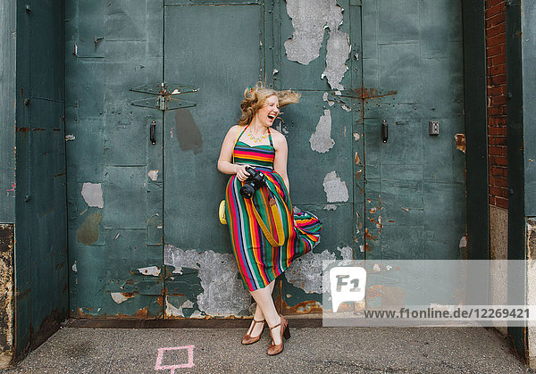 Young woman in striped dress leaning against industrial door laughing
