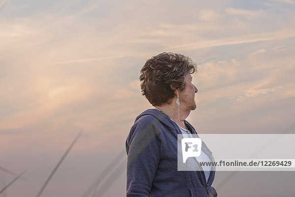 Woman with face turned away  sky in background