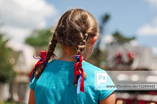 Mädchen mit geflochtenem Haar  rote und blaue Bänder im Haar  Rückenansicht