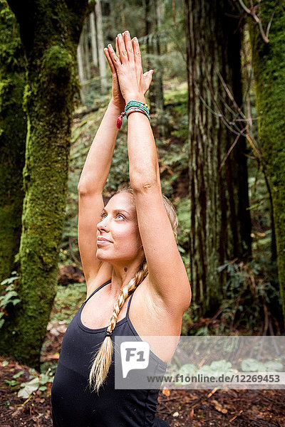Young woman practicing yoga in forest  meditating with hands together