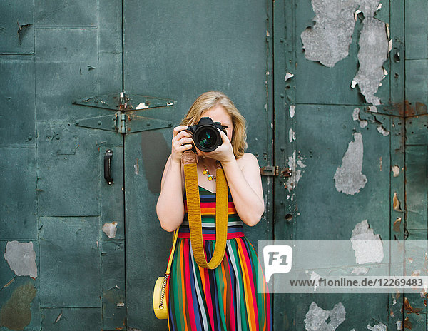 Young woman in striped dress in front of industrial door taking photographs  portrait