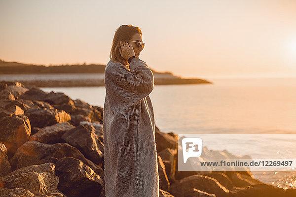 Porträt einer Frau mit Sonnenbrille und Wintermantel auf Felsen stehend und aufs Meer blickend  Odessa  Odeska Oblast  Ukraine  Osteuropa