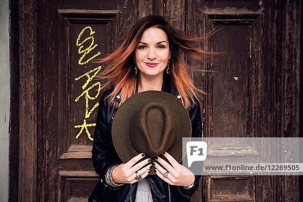 Porträt einer Frau  die einen Hut hält und in die Kamera schaut