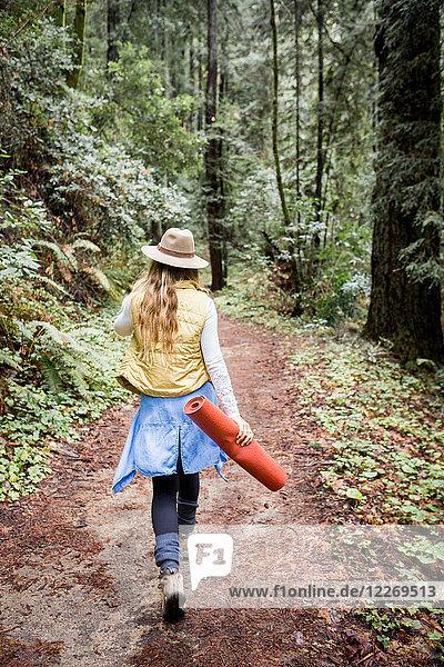 Junge Frau im Trilby beim Waldspaziergang  Rückansicht