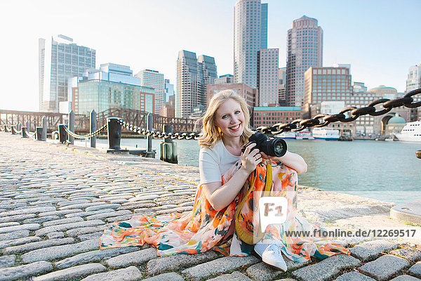 Young female photographer sitting on cobbled quayside,  portrait,  Boston,  Massachusetts,  USA