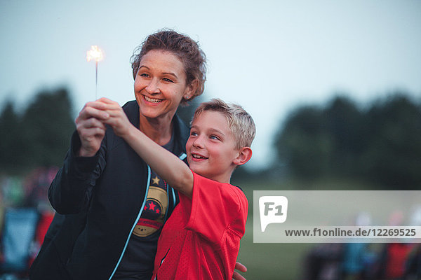Mother and son holding sparkler smiling