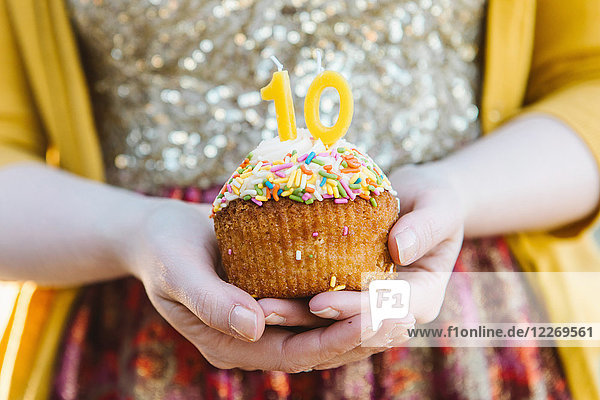 Young woman holding cupcake celebrating 10  mid section