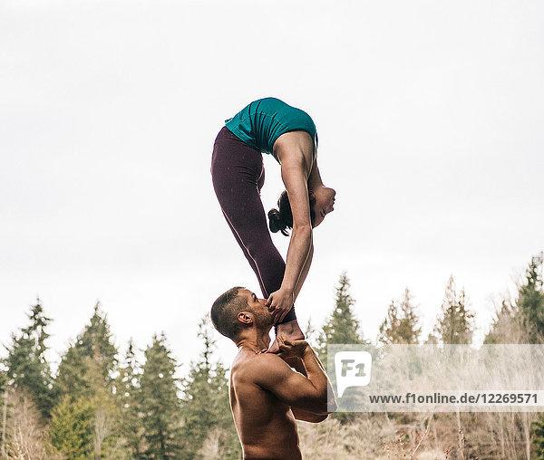 Couple practising acroyoga outdoors