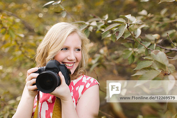 Young woman using DSLR camera in park